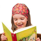 Laughing child reads a book Stock Images