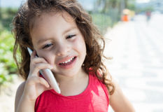 Laughing child in a red shirt speaking at phone outside. In a park with green plants in the background Stock Images