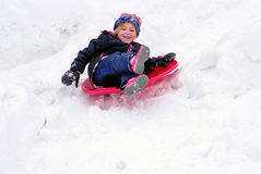 Laughing child sleds down a hill