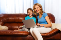 Laughing child and smiling mum with laptop Royalty Free Stock Photos