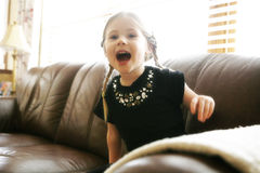 Laughing child on sofa. Portrait of laughing preschool girl on leather sofa or settee Stock Image