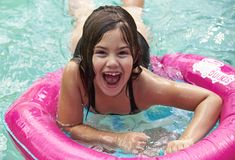 Laughing child swimming with pink float. Closeup of a laughing multiracial child swimming and leaning across a pink flotation ring Royalty Free Stock Photography