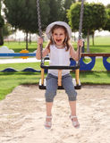 Laughing child on swing in summer park. Laughing little girl on swing in summer park Royalty Free Stock Images