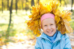 Laughing child wearing yellow autumn leaves Stock Images