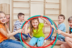 Laughing children. Laughing active children holding hula hoops Stock Images