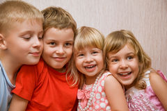 Laughing children in cosy room. Laughing children four together in cosy room, two pretty girls and two boys royalty free stock images