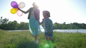 Laughing children in glasses run with balls on green lawn near river at leave. Laughing children in glasses run with balloons on green lawn near river at leave stock video