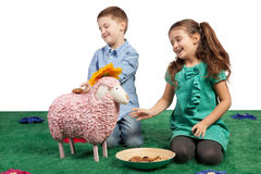 Laughing children playing with a toy sheep. Two laughing young children playing with a pink woolly toy sheep pretending to feed it with biscuits stock image