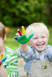 Laughing children showing colorful painted hands Royalty Free Stock Image