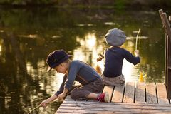 Laughing children sitting with sticks in hands. On the river bank Stock Photos
