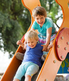 Laughing children on slide Royalty Free Stock Photography