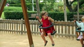 Laughing children on swing. In summer park stock video