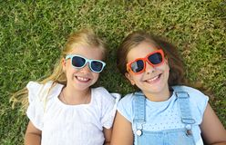 Laughing children wearing sunglasses relaxing during summer day royalty free stock photo