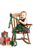 Laughing Christmas baby rocks in patchwork dress Royalty Free Stock Images