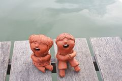 Laughing clay pottery dolls sitting on wood royalty free stock images