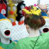 Laughing Clowns Amusement. Child with crazy hairdo standing in front of laughing clowns amusement at a school carnival, Brisbane 17 June 2012 Stock Photography