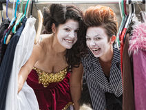 Laughing Clowns at Clothes Rack. Comedia Del Arte actors laughing at clothing rack Royalty Free Stock Images