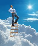 Laughing confident businessman standing at the top of ladder high in the sky Royalty Free Stock Images
