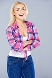 Laughing confident curvaceous blond woman. Standing with folded arms in a trendy checked knotted shirt and jeans  on grey Stock Photography