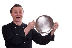 Laughing cook is upholding a pot Stock Photography