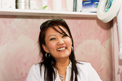 Laughing cosmetologist. Woman cosmetologist very laughs in his office Royalty Free Stock Image
