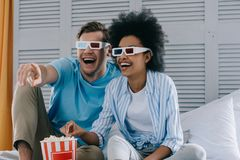 Laughing couple in anaglyph glasses watching movie at home. With popcorn stock images