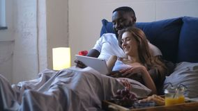 Young married couple watching comedy lying in bed. Laughing couple of beautiful blonde wife and handsome husband with dark skin hugging lying together in bed stock footage