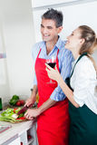 Laughing Couple Cooking in Kitchen Stock Photography