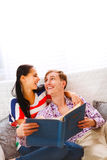 Laughing couple on couch looking photo album Stock Photography