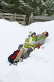 Laughing couple drinking from thermos and laying in snow together Stock Photos