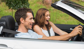 Laughing couple driving in a silver convertible Royalty Free Stock Photos