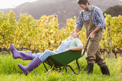 Laughing couple in dungarees pushing a wheelbarrow Royalty Free Stock Images