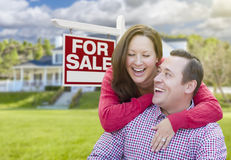Laughing Couple In Front of For Sale Sign and House Stock Photos