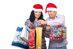 Laughing couple have fun with Christmas presents. Laughing couple with Santa hats brought Christmas presents  and the man trying to introduce a small gift box in Stock Photography