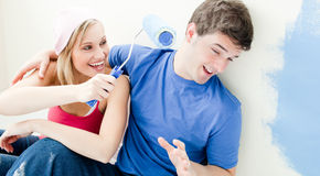 Laughing couple having fun while painting a room Royalty Free Stock Photos