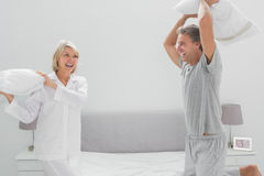 Laughing couple having a pillow fight Stock Photo