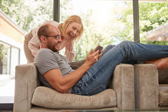 Laughing couple at home using digital tablet Stock Images