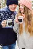 Laughing couple with hot drinks in cups in forest Stock Image