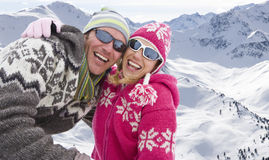 Laughing couple hugging on snowy mountain Stock Images