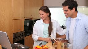 Laughing couple looking a recipe on a laptop stock footage