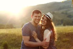 Laughing couple in love at sunset in nature, honeymoon, mountains, back light, soft light, emotions, laughing Stock Photography