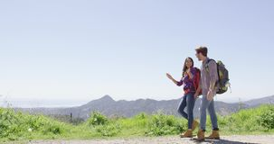 Laughing couple in mountains. Young laughing couple wearing backpacks and walking down road while hiking in mountains in summer time stock footage