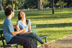 Laughing Couple on a Park Bench - Horizontal Royalty Free Stock Image