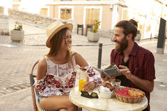 Laughing couple reading a guidebook outside a cafe in Ibiza royalty free stock images