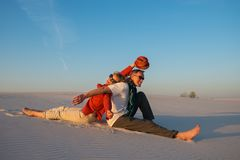 Laughing couple having fun in the desert. Laughing couple sitting, back to back, in the desert against a blue sky on a sunny evening, fools around and having fun Royalty Free Stock Image