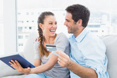 Laughing couple sitting on the couch shopping online with tablet pc Royalty Free Stock Photo