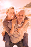 Laughing couple smiling at camera on the beach Stock Images