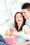 Laughing couple on sofa with popcorn and remote Stock Photos