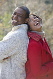 Laughing couple standing back to back outdoors Stock Photo