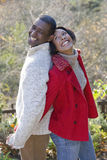 Laughing couple standing back to back outdoors stock image